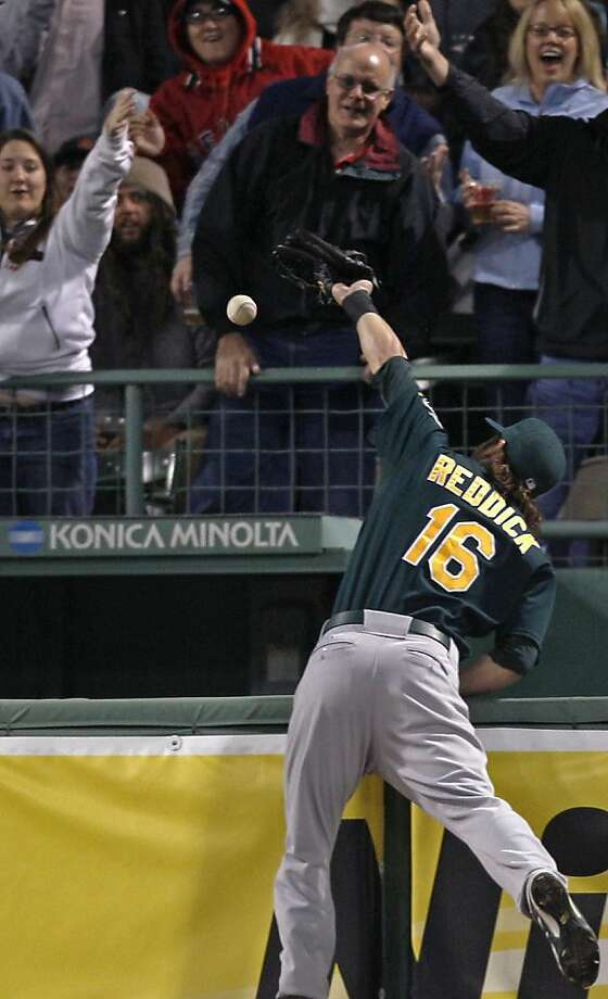 Oakland Athletics right fielder Josh Reddick (16) leaps but can't make the play on a solo home run by Boston Red Sox designated hitter David Ortiz (34) during the fifth inning of a baseball game at Fenway Park in Boston, Monday, April 30, 2012. (AP Photo/Charles Krupa) Photo: Charles Krupa, Associated Press