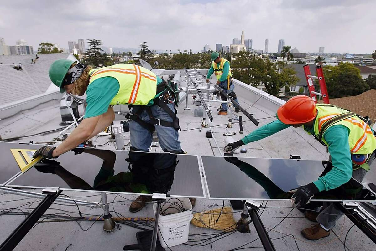 In this October 19, 2009 file photograph, newly hired photovoltaics installer Daniel Morabito, from left, of Hermosa Beach, Sal Sanchez and Victor Zapata installs thin film technology solar panels for SolarCity at the home of Andrew Kin in west Los Angeles, California. (Allen J. Schaben/Los Angeles Times/MCT)