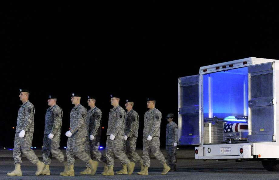 An Army carry team marches away from a transfer case containing the remains of Staff Sgt. Dick A. Lee Jr. Sunday, April 29, 2012 at Dover Air Force Base, Del. According to the Department of Defense, Lee, 31, of Orange Park, Fla., died April 26, 2012 in Ghazni province, Afghanistan from injuries sustained when his vehicle encountered an improvised explosive device. (AP Photo/Steve Ruark) Photo: Steve Ruark