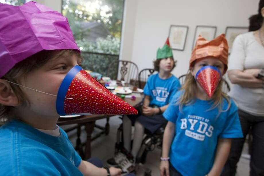 Next to his sister WIlla, 6, right, and brother Peter, 10, Aaron, left, celebrates his 9th birthday before school Monday, April 23, 2012, in Bellarie. (Johnny Hanson / Houston Chronicle)