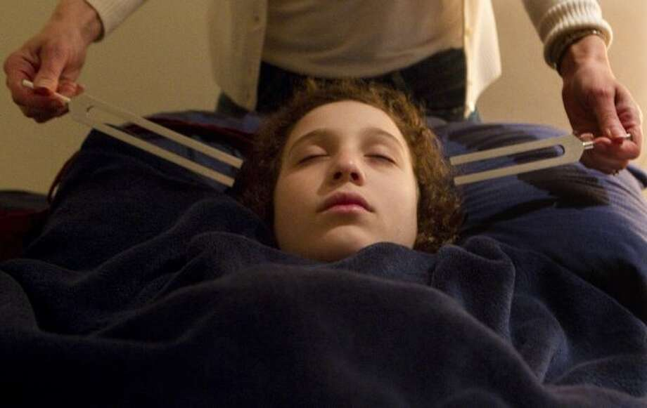 Peter Berry falls asleep as family friend, Laurie Levin performs sound healing to Aaron as he prepared for bed Monday, March 12, 2012, in Bellaire. Levin, who performs the healing exercises a couple times a month said she has seen increased responses by both Peter and Aaron because of the treatment on the boys who are both paralyzed from the waist down. (Johnny Hanson / Houston Chronicle)