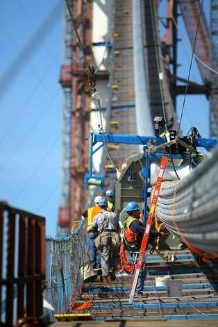 Crew men work to complete the compressing process of the suspension cable of the new Bay Bridge Monday, April 30, 2012. The compaction process shapes 137 strands of cable into one. The work is set to be complete next week. Photo: Erik Verduzco, The Chronicle