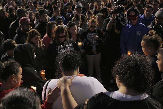 Solialofi Ieremia, bottom center, is comforted by family and friends during a candlelight vigil for her nephew Osana Futi on Monday. Friends and family of Osana Futi gathered at Newark Memorial High School in Newark, Calif.,  on Monday, April 30, 2012, to pay tribute to the teen who was killed on Saturday night. Photo: Carlos Avila Gonzalez, The Chronicle