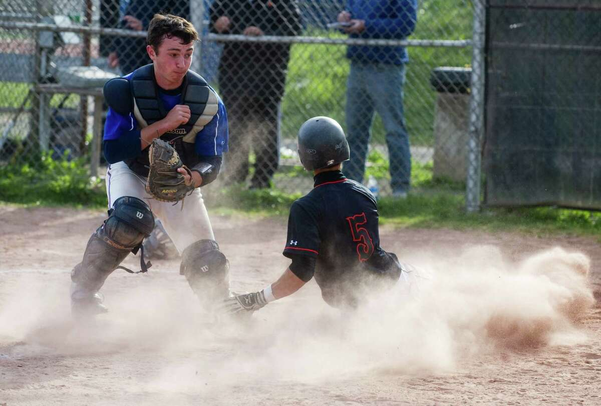 Stamford's Travis Docimo heads home as Danbury's Jack Zanine covers the plate Stamford High School hosts Danbury in a baseball game in Stamford, Conn., Sunday, April 30, 2012. Docimo was safe.