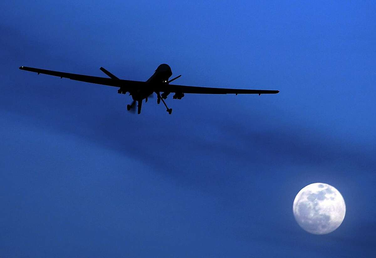 FILE - In this Jan. 31, 2010 file photo, an unmanned U.S. Predator drone flies over Kandahar Air Field, southern Afghanistan, on a moon-lit night. The White House has no intentions to end CIA drone strikes against militant targets on Pakistani soil, setting the two countries up for diplomatic blows after Pakistani's parliament unanimously approved new guidelines for the country in its troubled relationship with the US, US and Pakistani officials say. (AP Photo/Kirsty Wigglesworth, File)