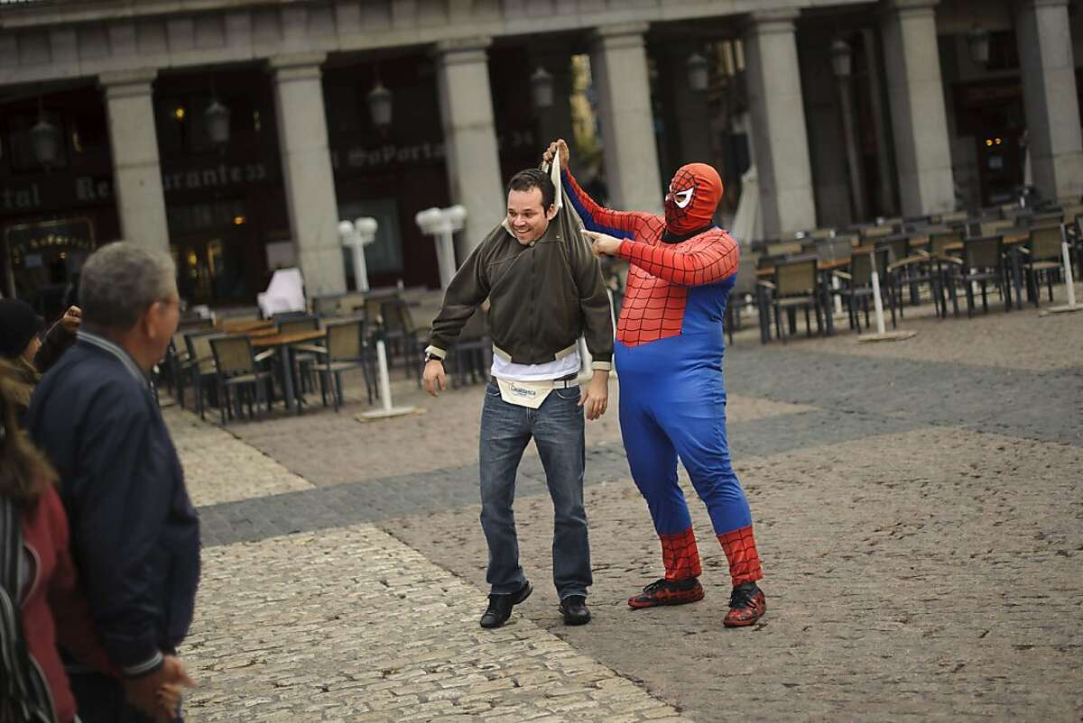 A man dressed as comic super-hero Spiderman performs with a tourist while they pose for pictures in the Plaza Mayor, in Madrid, Monday, April 30, 2012.(AP Photo/Daniel Ochoa de Olza)