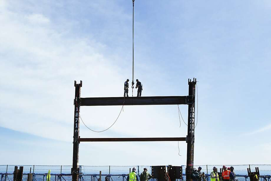 Steel workers Jim Brady, right, and Billy Geoghan walk onto a steel beam after maneuvering it into place on the 100th story of One World Trade in New York, Monday, April 30, 2012. The addition of steel columns to the 100th story pushed the height of One World Trade above that of the Empire State Building today. (AP Photo/Lucas Jackson, Pool) Photo: Lucas Jackson, Associated Press