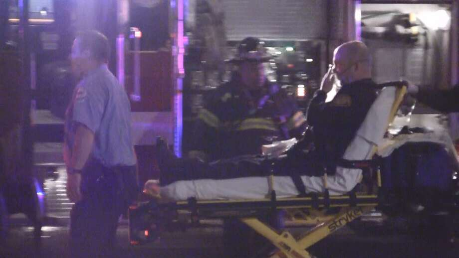 A Bridgpeort firefighter is taking away on a stretcher after suffering from smoke inhalation at a fire the night of Monday, April 30, 2012 on State Street in Bridgeport, Conn. Photo: Stephen Krauchick