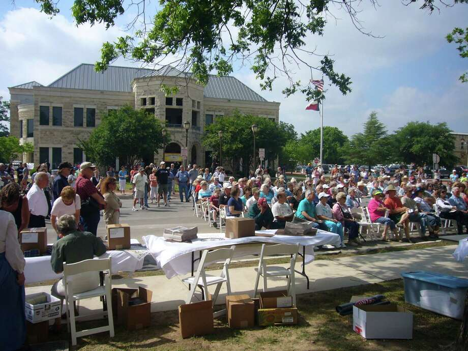 Attendees gather at the Historic Kendall County Courthouse for opening ceremonies of the Kendall County sesquicentennial on April 28. In the background is the new courthouse that houses most county offices. Photo: Photo By Linda Byrne