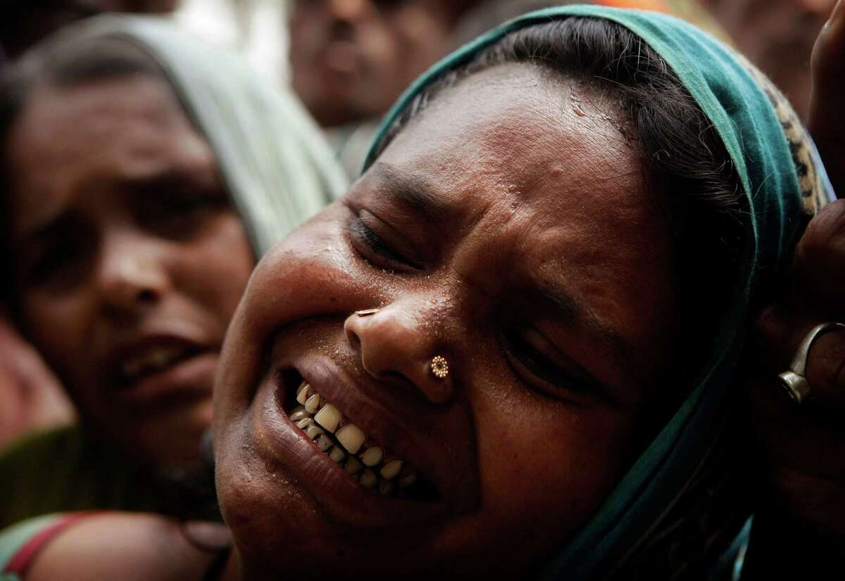 A relative cries near the dead body of a person who died after a ferry capsized in the Brahmaputra River at Buraburi village, about 350 kilometers (215 miles) west of the state capital Gauhati, India, Tuesday, May 1, 2012. Army divers and rescue workers pulled more than 100 bodies out of a river after a packed ferry capsized in heavy winds and rain in remote northeast India, an official said Tuesday. At least 100 people were still missing Tuesday after the ferry carrying about 350 people broke into two pieces late Monday, said Pritam Saikia, the district magistrate of Goalpara district.