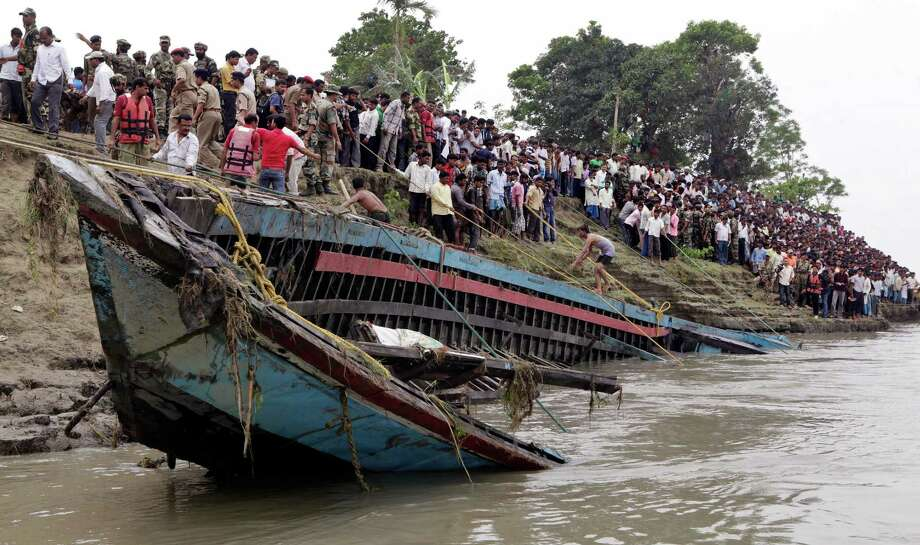 Rescuers pull out the wreckage of a ferry that capsized in the Brahmaputra River at Buraburi village, about 350 kilometers (215 miles) west of the state capital Gauhati, India, Tuesday, May 1, 2012.   Army divers and rescue workers pulled more than 100 bodies out of a river after a packed ferry capsized in heavy winds and rain in remote northeast India, an official said Tuesday. At least 100 people were still missing Tuesday after the ferry carrying about 350 people broke into two pieces late Monday, said Pritam Saikia, the district magistrate of Goalpara district. Photo: Anupam Nath, AP / AP