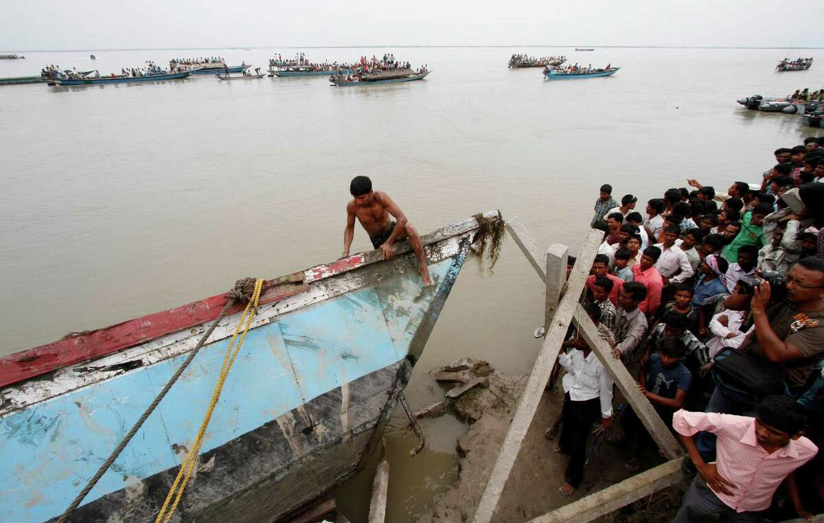 A local villager climbs up to look for survivors in the wreckage of a ferry that capsized in the Brahmaputra River at Buraburi village, about 350 kilometers (215 miles) west of the state capital Gauhati, India, Tuesday, May 1, 2012. Army divers and rescue workers pulled more than 100 bodies out of a river after a packed ferry capsized in heavy winds and rain in remote northeast India, an official said Tuesday. At least 100 people were still missing Tuesday after the ferry carrying about 350 people broke into two pieces late Monday, said Pritam Saikia, the district magistrate of Goalpara district.