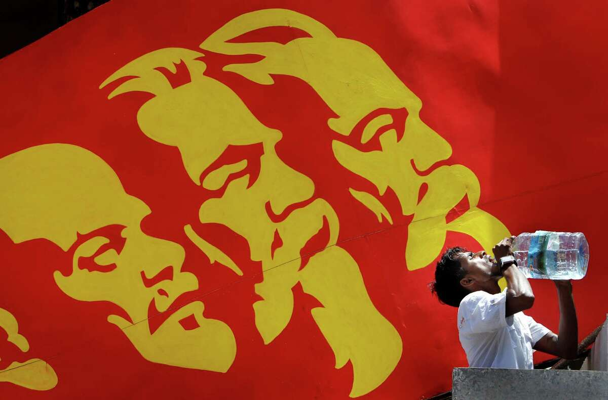 An activist of Sri Lanka's Marxist political party, People's Liberation Front, drinks water from a bottle as a billboard of Communist leaders from left, Vladimir Lenin, Karl Marx and Friedrich Engels is displayed in the background during a street march to celebrate international Labor Day known as May Day in Colombo, Sri Lanka, Tuesday, May 1, 2012. May Day moved beyond its roots as an international workers' holiday to a day of international protest Tuesday, with rallies throughout Asia demanding wage increases and marches planned across Europe over government-imposed austerity measures.