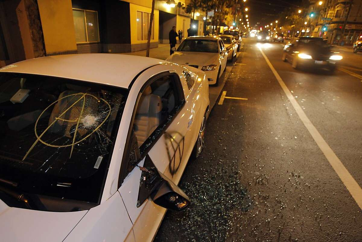 A vandalized Ford Mustang sits on Valencia Street on Monday night after vandals with the Occupy march broke the windows and spray painted the car. Police and merchants were hit by vandals along Valencia Street in San Francisco, Calif., on Monday, April 30. 2012.