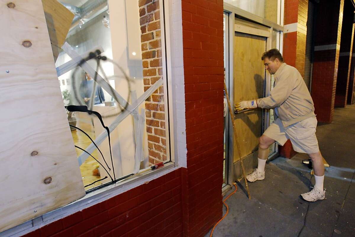 Eric Koehler, manager of Artzone 461 Gallery, works to shut the gallery's door after fitting it with plywood on Monday night after vandals with the Occupy march broke the windows and door of the gallery. Police and merchants were hit by vandals along Valencia Street in San Francisco, Calif., on Monday, April 30. 2012.