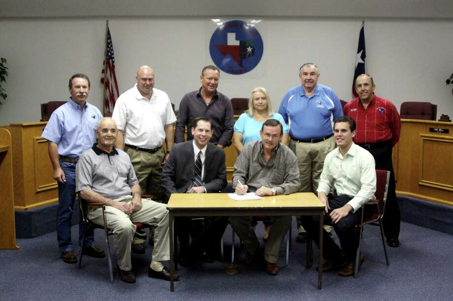 Representatives from Altus HMS, the Lumberton Industrial Development Corporation, and City of Lumberton gathered to sign the contract that will provide a $300,000 loan to the Healthcare company to help secure an emergency facility in Lumberton. Pictured; front row, from left, Mayor Don Surratt, Kevin Herrington, Altus Regional Senior Vice President, Rickey Simmons, IDC President, Josh Young, Altus Project Manager; back row, from left, City Attorney Curtis Soileau, Kenneth Wahl, Andy Kelley, Lynette Barks, Council members, City Manager Steve Clark. Photo: David Lisenby, HCN_Altus Signing