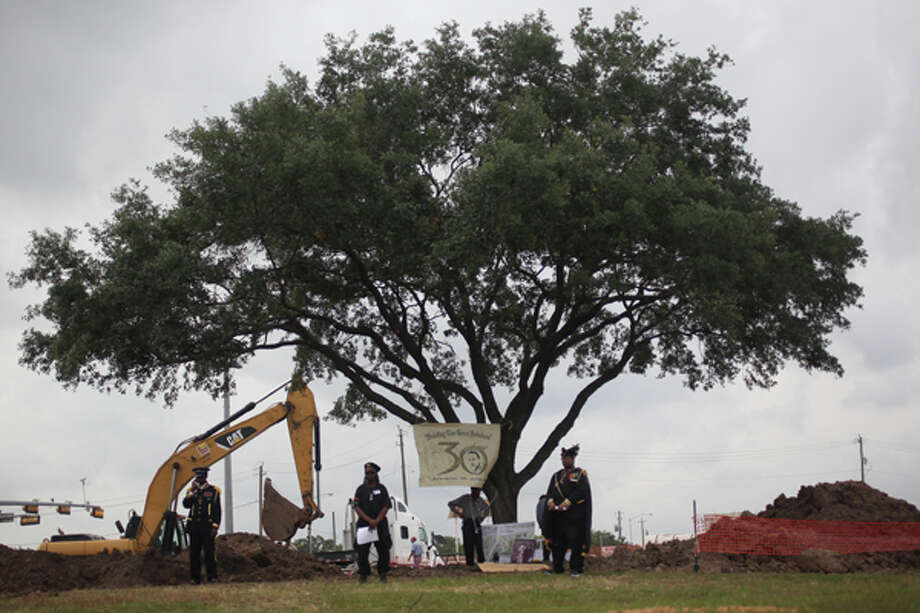 "Members of the People's Party lll stand guard at the ""tree if life"" at OST and MLK. (Chronicle)"