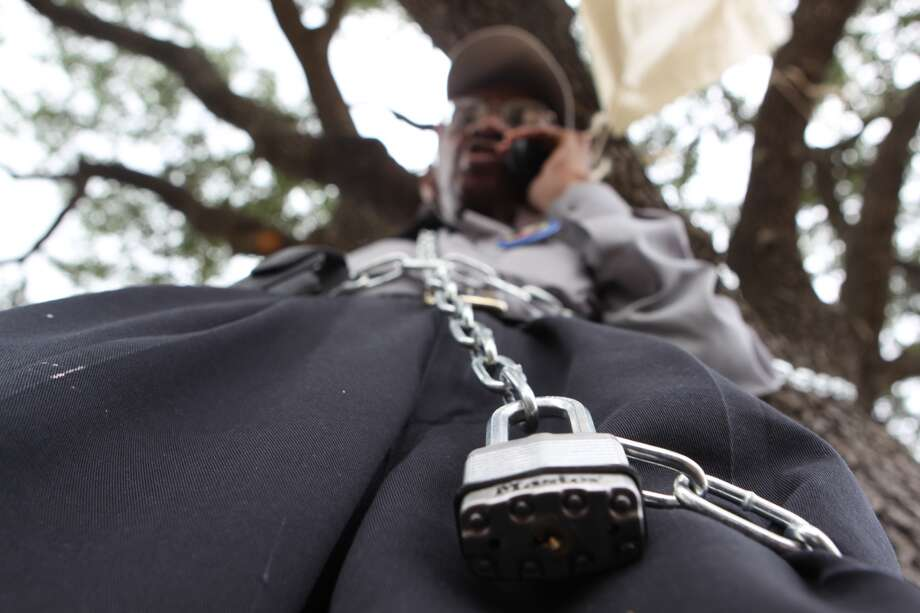 Ovide Duncantell, founder of the Black Heritage Society, chained himself to the tree on Old Spanish Trail and Martin Luther King in protest of its upcoming move to MacGregor Park.