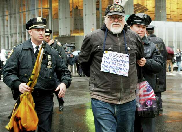 Police escort away a man who was arrested as members of Occupy Wall Street protest during a May Day rally in front of the Bank of America in New York City. Demonstrators have called for nation-wide May Day strikes to protest economic inequality and political corruption. Photo: Monika Graff, Getty Images / 2012 Getty Images