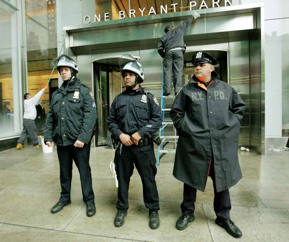 Members of the New York Police Department  stand guard in front of the Bank of America building at One Bryant Park while members of Occupy Wall Street protest during a May Day rally out front on Tuesday in New York City. Demonstrators have called for nation-wide May Day strikes to protest economic inequality and political corruption. Photo: Monika Graff, Getty Images / 2012 Getty Images