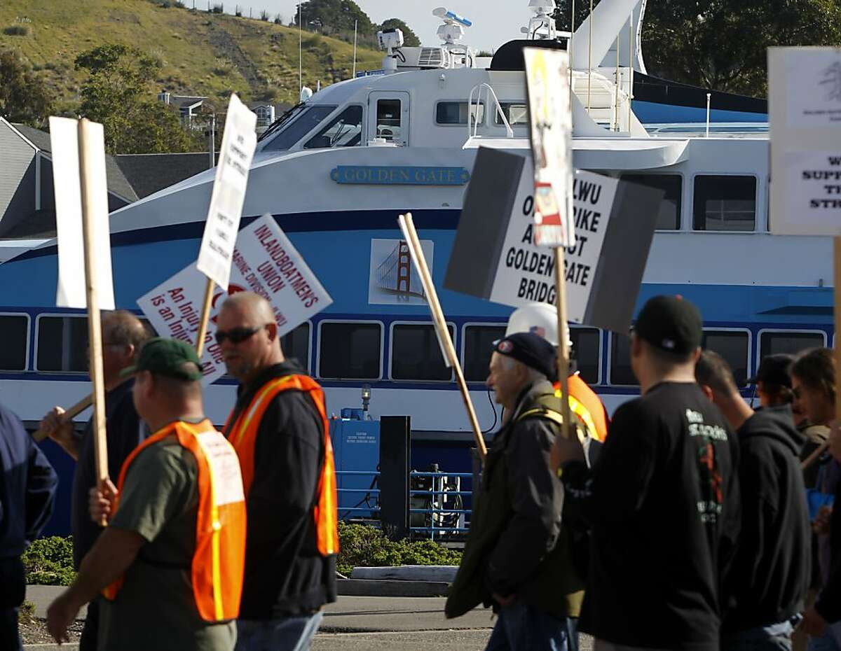 Striking transit workers and supporters march past an idle ferry boat at the Golden Gate Transit ferry terminal in Larkspur, Calif. on Tuesday, May 1, 2012.