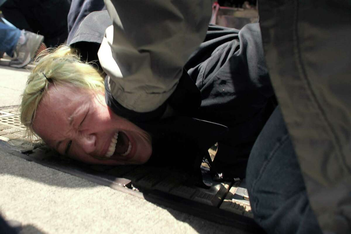 NEW YORK, NY - MAY 01: A protester associated with the Occupy Wall Street movement is arrested while marching through traffic in lower Manhattan on May 1, 2012 in New York City. May 1st, Labor Day, is a traditional day of global protest in sympathy with union and leftist politics.