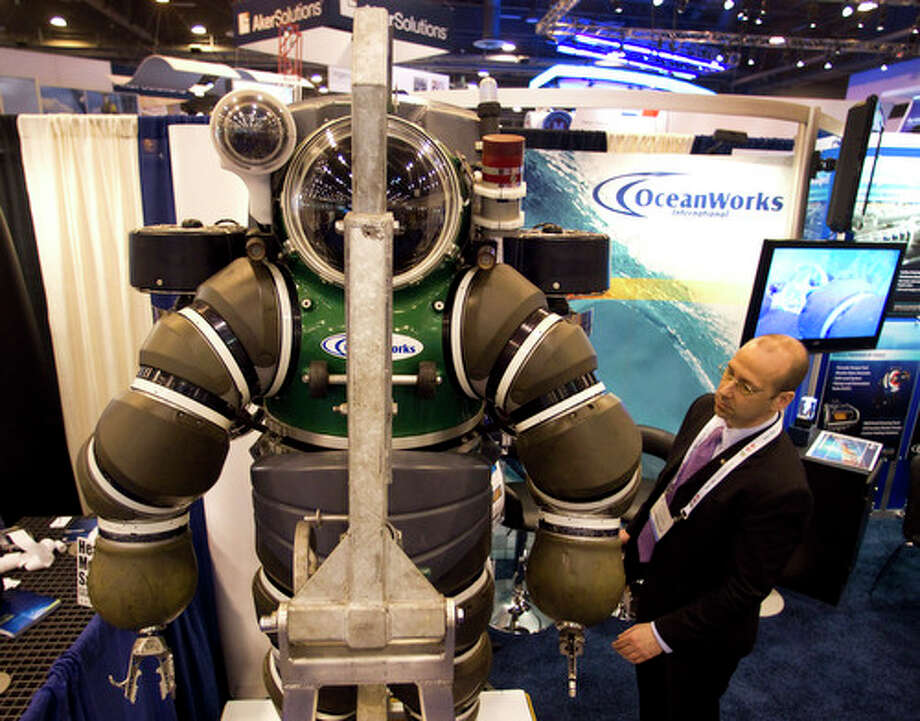 Robert Hawkins takes a look at the Hardsuit Quantum II diving system from Oceanworks International is shown on display during the 2012 Offshore Technology Conference Tuesday, May 1, 2012, in Houston. Photo: Brett Coomer, Houston Chronicle / © 2012 Houston Chronicle