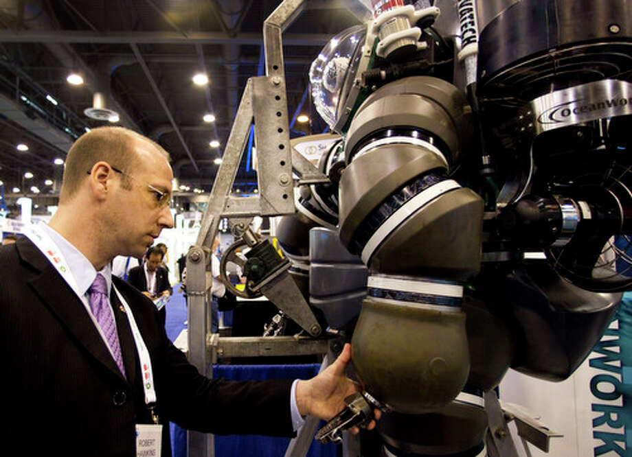 "Robert Hawkins looks at the ""hand"" of the Hardsuit Quantum II diving system from Oceanworks International is shown on display during the 2012 Offshore Technology Conference Tuesday, May 1, 2012, in Houston. Photo: Brett Coomer, Houston Chronicle / © 2012 Houston Chronicle"