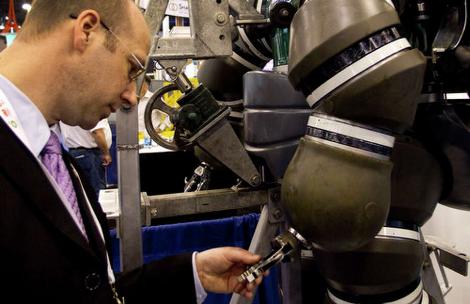 """Robert Hawkins looks at the """"hand"""" of the Hardsuit Quantum II diving system from Oceanworks International is shown on display during the 2012 Offshore Technology Conference Tuesday, May 1, 2012, in Houston. Photo: Brett Coomer, Houston Chronicle / © 2012 Houston Chronicle"""