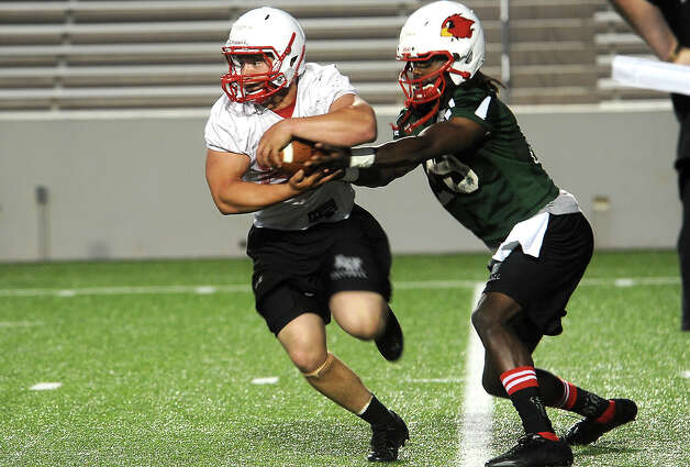 Lamar's Caleb Harmon takes the hand off from Jeremy Johnson at Lamar University in Beaumont, Wednesday, March 21, 2012. Tammy McKinley/The Enterprise Photo: TAMMY MCKINLEY