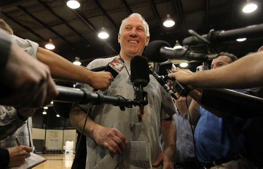 Spurs head coach Gregg Popovich cracks a smile during a question and answer session with media as players for the San Antonio Spurs attend their first team practice on Friday, Dec. 9, 2011.  Kin Man Hui/kmhui@express-news.net (KIN MAN HUI / SAN ANTONIO EXPRESS-NEWS)