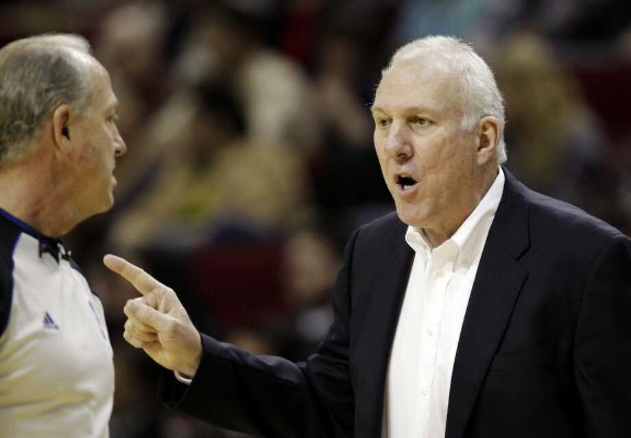 San Antonio Spurs coach Gregg Popovich, right, talks to official Kevin Fehr, left, during the second quarter of an NBA basketball game against the Houston Rockets, Thursday, Dec. 29, 2011, in Houston. (AP Photo/David J. Phillip) (AP)