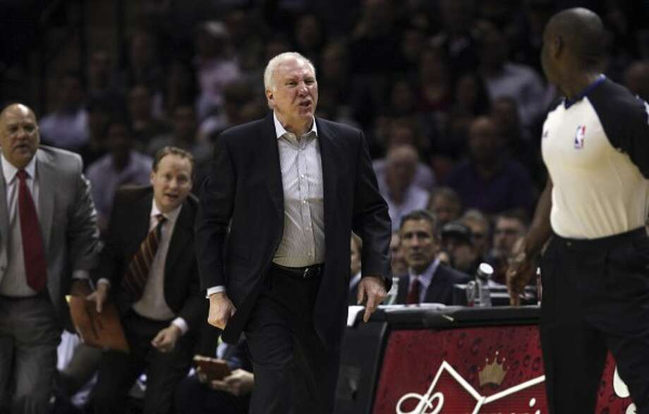 SPURS -- San Antonio Surs head coach Gregg Popovich goes after official James Williams as assistant coaches Don Newman, left and Mike Budenholzer try to keep him away during the second half against the New York Knicks at the AT&T Center, Wednesday, March 7, 2012. Popovich was eject in the process. The Spurs won 118-105. Jerry Lara/San Antonio Express-News (San Antonio Express-News)