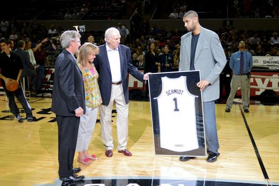 San Antonio Spurs center Tim Duncan (right) and San Antonio Spurs head coach Gregg Popovich present a jersey to David R. Schmidt, M.D. and Becky Whetstone, Ph.D who's son Marine Lance Cpl. Benjamin Whetstone Schmidt was killed during a combat mission in the Helmand province in Afghanistan, where he was a scout sniper, on October 6, 2011. The presentation was made before a NBA basketball game between the Philadelphia 76ers and the San Antonio Spurs at the AT&T Center in San Antonio, Texas on March 25, 2012. John Albright / Special to the Express-News. (San Antonio Express-News)