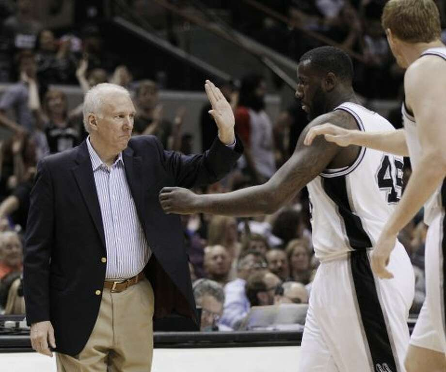 San Antonio Spurs coach Gregg Popovich, left, greets his players during a timeout in the fourth quarter of an NBA basketball game against the Portland Trail Blazers, Monday, April 23, 2012, in San Antonio. San Antonio won 124-89, clinching the top seed in the Western Conference. (AP Photo/Eric Gay) (AP)