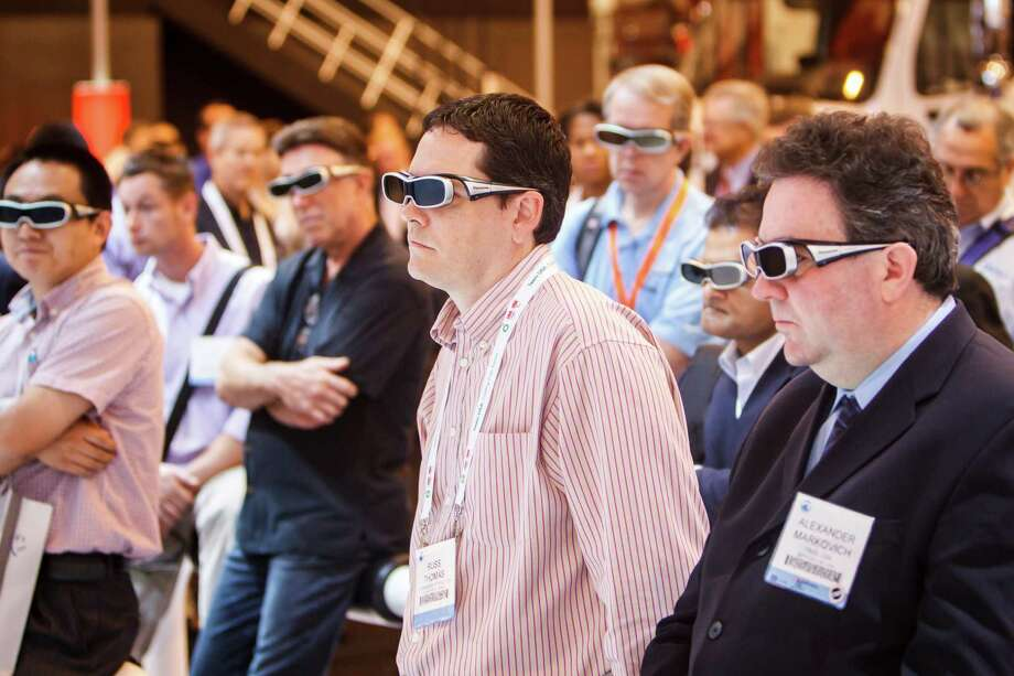 Russ Thomas, center, and others watch a 3-D presentation at the Siemens booth during the 2012 Offshore Technology Conference at Reliant Park, Tuesday, May 1, 2012, in Houston. Photo: Michael Paulsen, Houston Chronicle / © 2012 Houston Chronicle