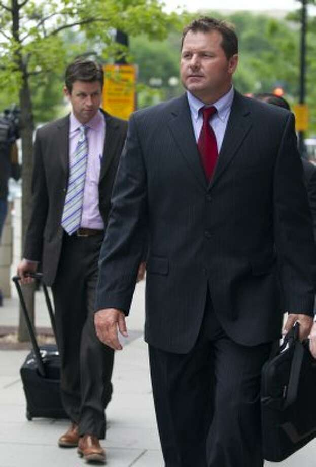 Former Major League Baseball pitcher Roger Clemens, right, leaves the Federal Court in Washington as a perjury retrial of the seven-time Cy Young Award winning pitcher entered its third week Monday, April 30, 2012.   (Manuel Balce Ceneta / Associated Press)