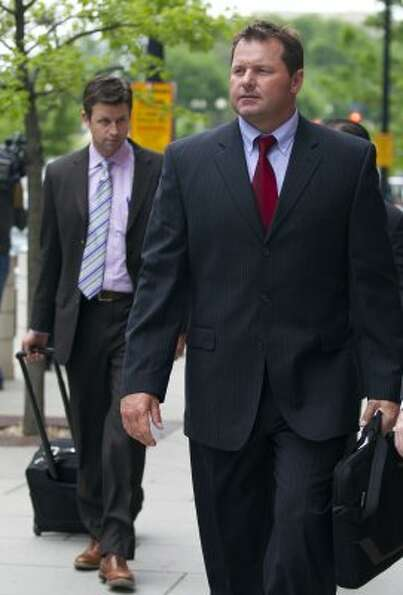 Former Major League Baseball pitcher Roger Clemens, right, leaves the Federal Court in Washington as