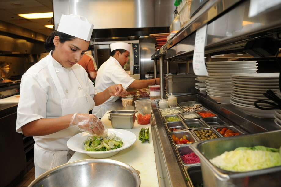 Mariana Martinez, of The Woodlands, prepares a Bistro Salad at the Hubbell & Hudson Bistro in The Woodlands. Photo: Jerry Baker