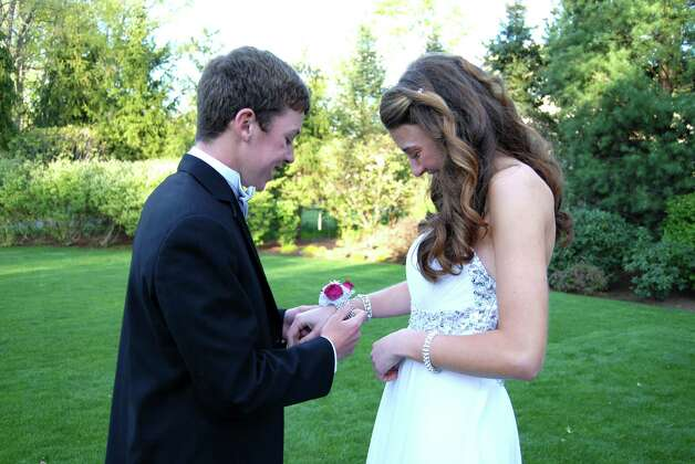 Mike Slattery puts the corsage on his junior prom date Courtney Cole at a pre-prom party, Friday night, April 27, 2012.  Photo by Savannah Shepard. Photo: Contributed Photo