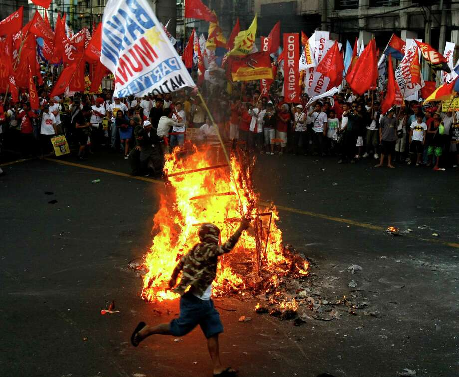 Protesters dance around the burning effigy of Philippine President Benigno Aquino III during a rally near the Presidential Palace in Manila to celebrate international Labor Day known as May Day Tuesday May 1, 2012 in the Philippines. Thousands of workers marched under a brutal sun in Manila to demand a wage increase amid an onslaught of oil price increases, but the Philippine President rejected a $3 daily pay hike which the workers have been demanding since 1999 and warned may worsen inflation, spark layoffs and turn away foreign investors. (AP Photo/Bullit Marquez) Photo: Bullit Marquez, Associated Press / AP