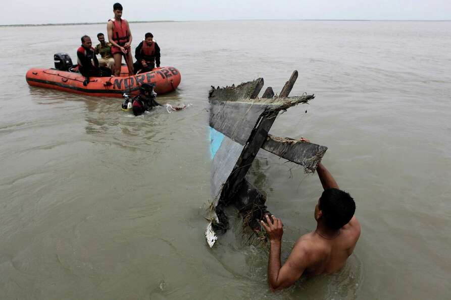 Rescuers pull out the wreckage of a ferry that capsized in the Brahmaputra River at Buraburi village