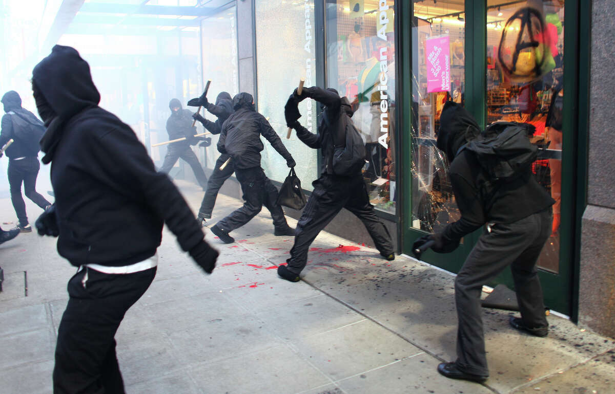 Black-clad protesters break windows on downtown businesses including American Apparel and NikeTown during a May Day rally.