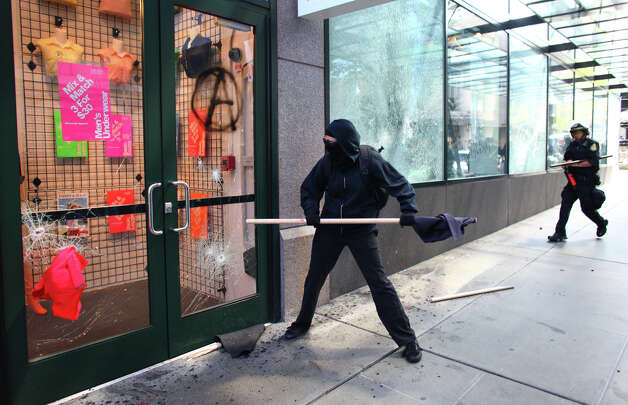 A Seattle police officer runs up on a black-clad protester breaking windows at American Apparel and NikeTown during a May Day rally. Photo: JOSHUA TRUJILLO / SEATTLEPI.COM