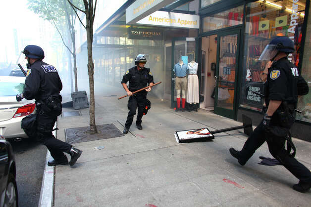 Seattle Police officers clear an area after black-clad protesters shattered windows during a May Day rally. Photo: JOSHUA TRUJILLO / SEATTLEPI.COM