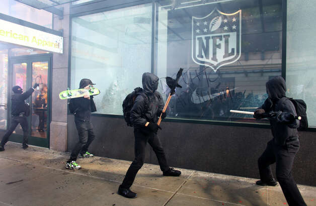 Black-clad protesters break windows on downtown businesses including American Apparel and NikeTown. Photo: JOSHUA TRUJILLO / SEATTLEPI.COM