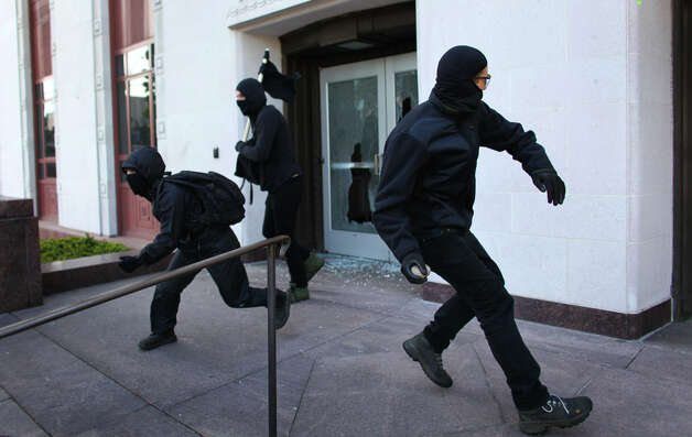Black-clad protesters break windows on the old Federal Courthouse as a May Day rally turns violent. Photo: JOSHUA TRUJILLO / SEATTLEPI.COM