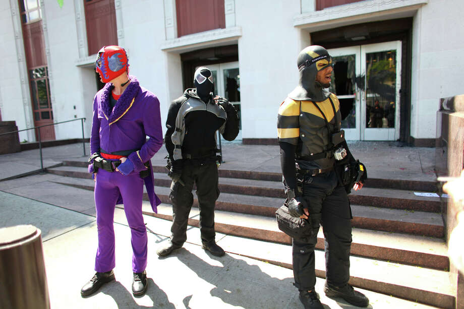 From left, self-described super heroes Caballero, Midnight Jack and Phoenix Jones stand in front of the downtown Seattle Federal Courthouse after they released pepper spray on protesters that were smashing windows there. Photo: JOSHUA TRUJILLO / SEATTLEPI.COM