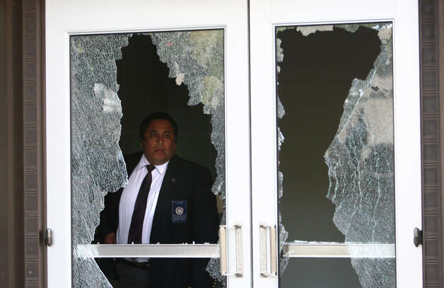 A court security officer looks through a broken window after black-clad protesters shattered windows on the downtown Federal Courthouse. Photo: JOSHUA TRUJILLO / SEATTLEPI.COM