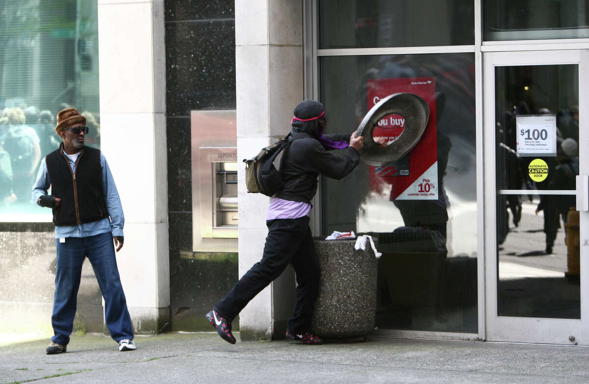 A black-clad protester attempt to break windows on a Bank of America during a May Day rally on Tuesday, May 1, 2012 in downtown Seattle.